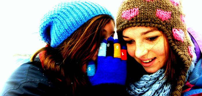 Two girls whispering secrets